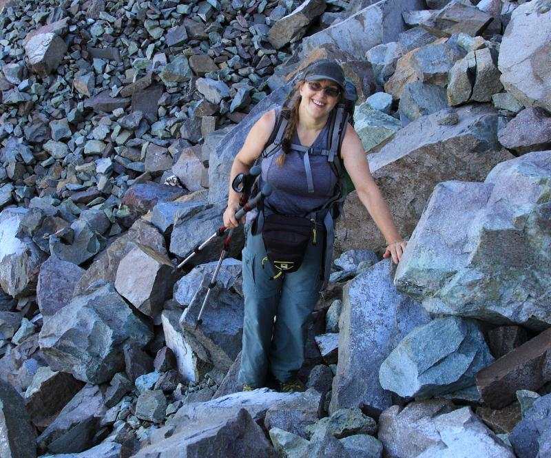 Female hiker leaning on boulders with hiking poles and backpack