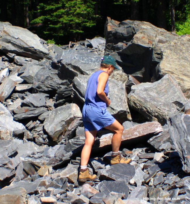 Female hiker wearing heavy leather hiking boots on a rocky slope