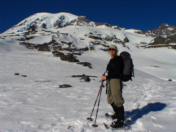Female snowshoer on flank of Mount Rainier with backpack and trekking poles