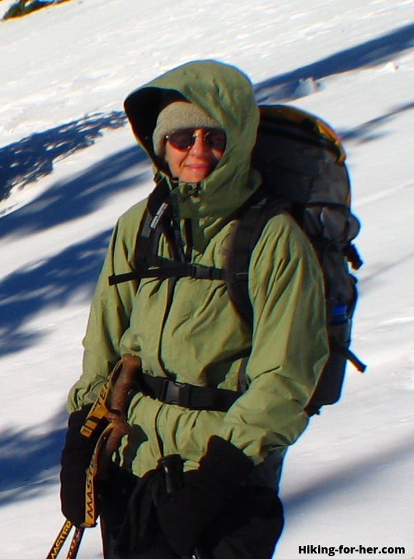 Female hiker bundled up against the cold while crossing a snowfield, wearing a backpack and carrying trekking poles