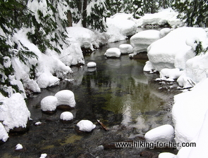 Wintery stream with snow piled on rocks like fluffy pillows