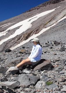 Female hiker sitting on a rock in a pile of rocky debris on a mountainside