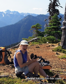 Surprised female hiker sitting on a hiking trail with her backpack