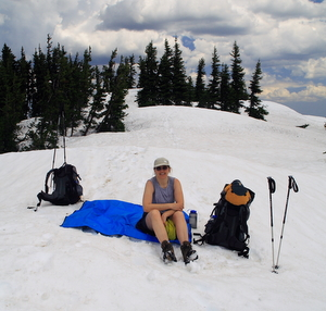 Female hiker sitting on a blue tarp in the snow surrounded by her hiking gear