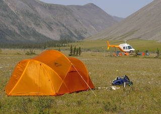 Orange tent in the backcountry with orange and white helicopter in the background waiting to transport us to a new location