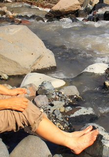 Bare feet resting on rocks beside a rushing mountain stream