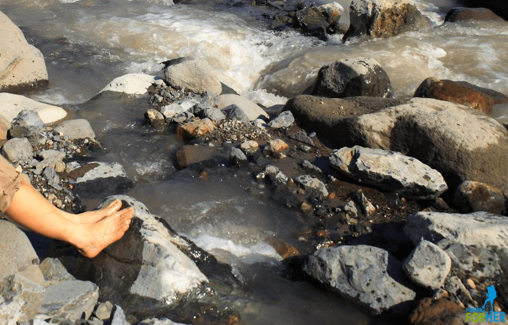 Feet of a hiker soaking in an icy glacier melt stream, with lots of boulders