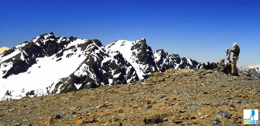 Female hiker looking at her gear with snowy mountain in background