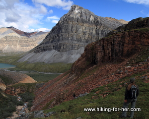 Female hiker gazing at stratified rocks in a mountainside