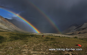 Double rainbow across a blackened sky, with hiking tents in foreground