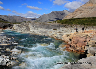 Rushing mountain river surrounded by rocky outcrops with two hikers exploring the banks