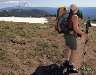 Female backpacker with hiking poles on the Pacific Crest Trail with Mount Adams in background