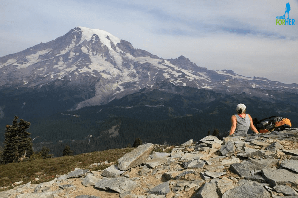 Female hiker resting on rocky alpine ridge and gazing at Mount Rainier across the Nisqually River Valley