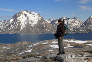 Female hiker with snow covered mountains behind her in East Greenland