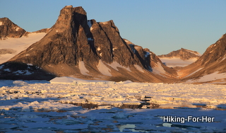 Icy bay with big mountains in the distance in East Greenland