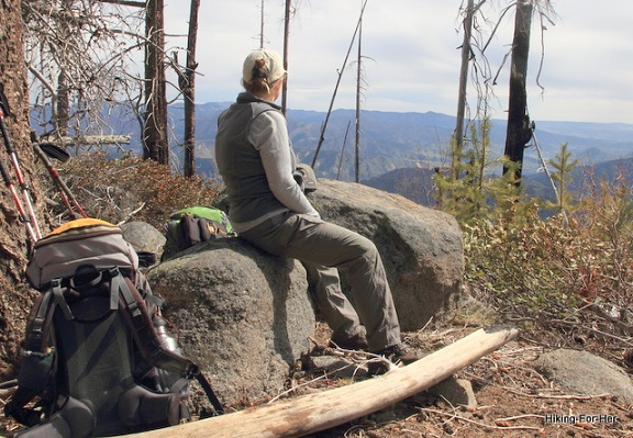 Female hiker facing away, seated on a large gray boulder