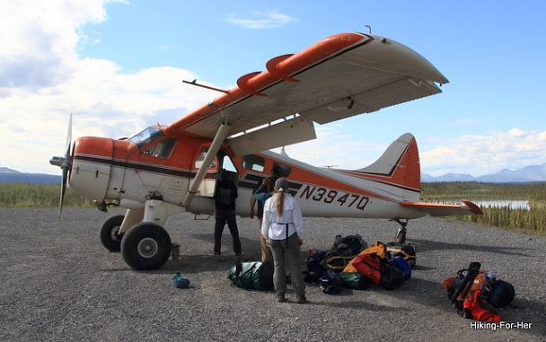 Bush plane loading up backpacking gear with a female hiker amongst the camping gear