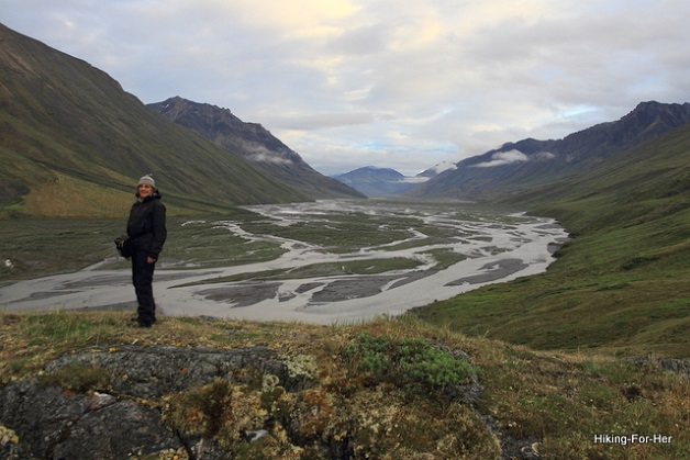 female hiker dressed in rain gear, looking down at the Canning River braiding through a valley in ANWR Alaska
