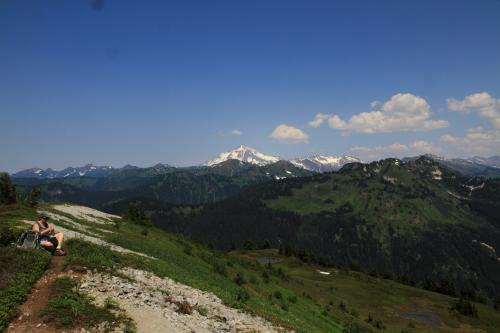 Hiker taking a snack break on an alpine trail with snowy mountains in distance