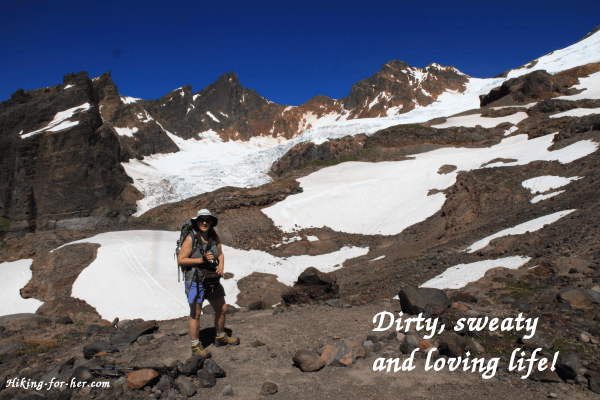 Mount Baker in background of female hiker with pack, poles and hiking boots: dirty, sweaty and loving life!