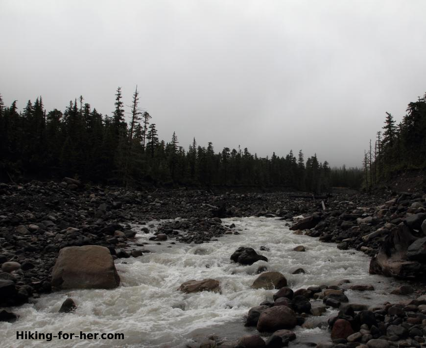 Gray, cloudy day hiking along a roaring river