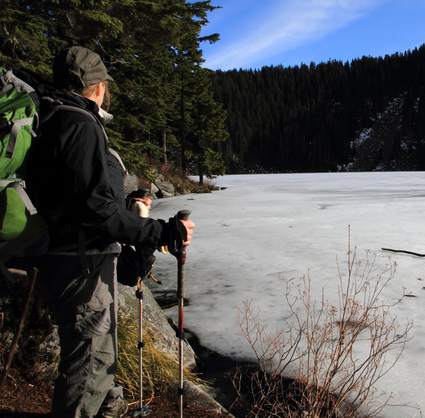 Female hiker with green backpack and trekking poles looking at frozen alpine lake