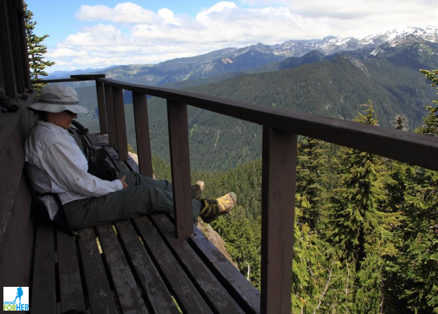 Female hiker sitting down and dangling feet off deck of fire lookout