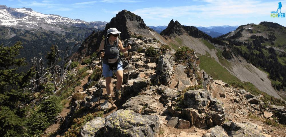 Female hiker with trekking poles on rocky Plummer Peak, Mount Rainier National Park