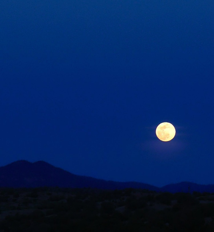 Full moon rising over the hills in a dark blue sky