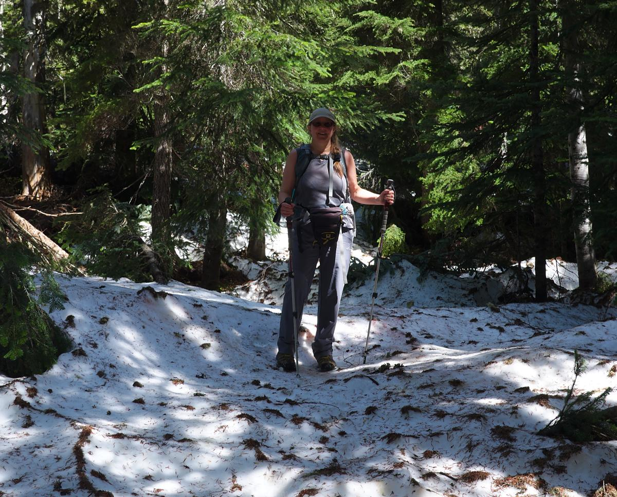 Female hiker on snow using trekking poles for balance
