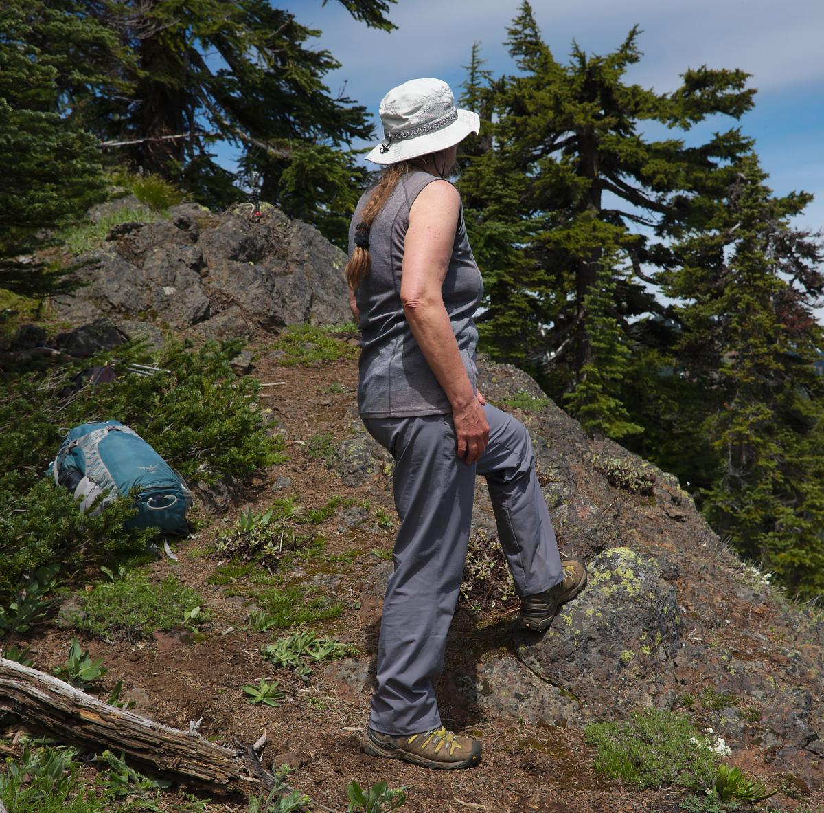 Female hiker at rest stop on ridge top, wearing moisture wicking hiking pants and shirt, boots and sun hat.