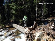 Female hiker wearing green backpack crossing a log over a rushing stream