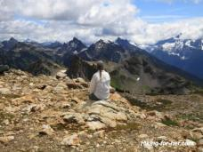 Female hiker sitting on rocks in high alpine terrain