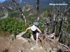 Female hiker climbing tree roots on rocky mountain slope