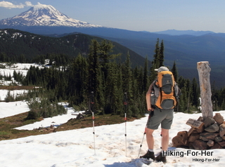 Female hiker standing on snow wearing yellow and gray backpack with trekking poles planted  near a hiking trail sign with Mount Adams in the distance