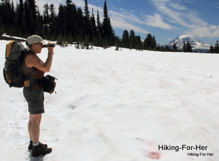 Female hiker wearing a backpack standing on a snow field while taking photos