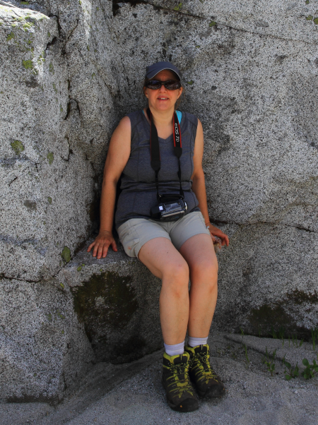 Female hiker sitting in a rock crevice