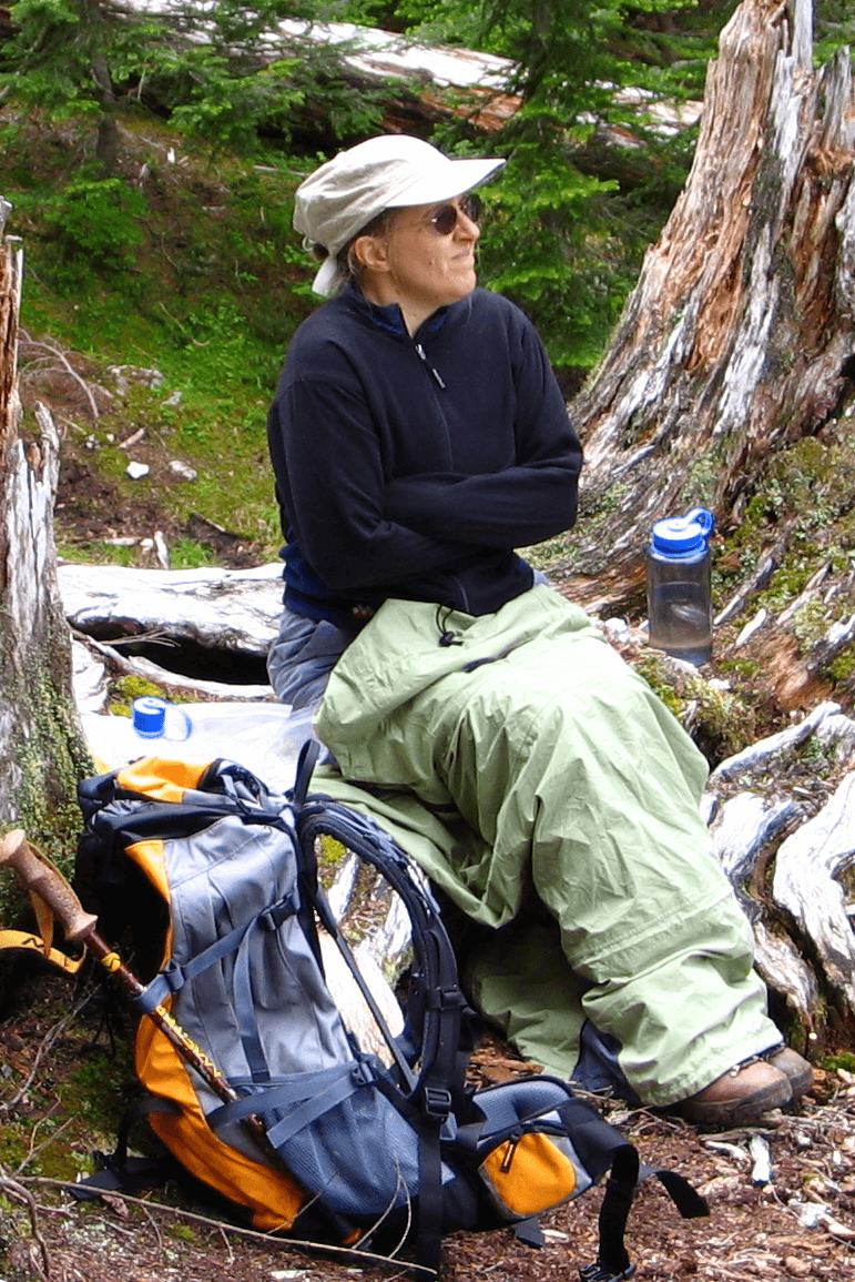 Female hiker sitting on a log with arms crossed looking cold and tired, with backpacking gear spread around her