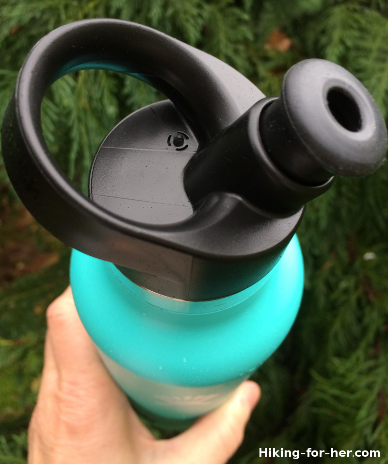 Green Hydroflask with sports cap in a hiker's hand