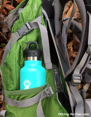 Green 21 oz Hydroflask in mesh pocket on a hiking backpack