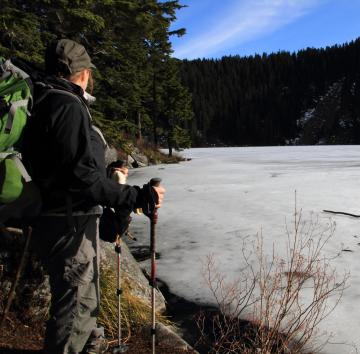 Hiker wearing green backpack, standing at edge of frozen lake on a winter hike