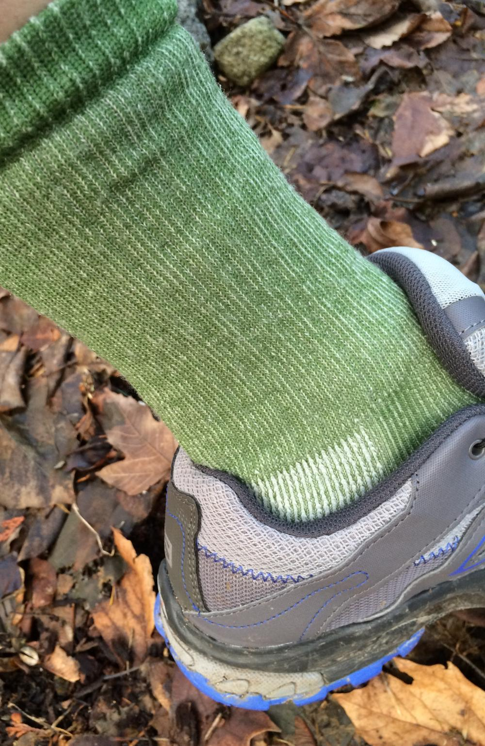 Green hiking sock in a gray and blue trail shoe