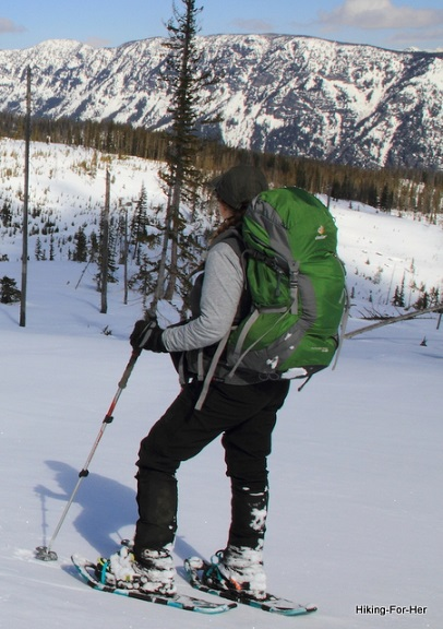 Female snowshoer wearing a green pack in the mountains