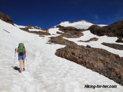 Hiker wearing green backpack hiking up a snow field
