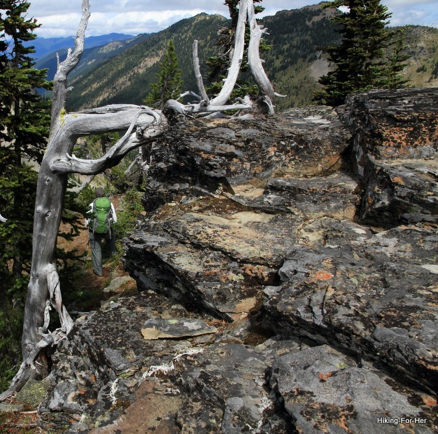 Backpacker with green pack negotiating rocky terrain