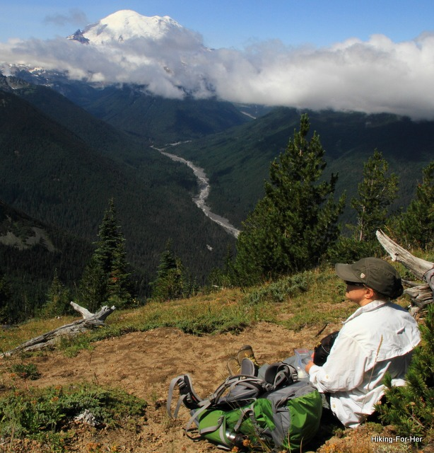 Female hiker looking across the valley at the White River cascading down the flank of Mt. Rainier