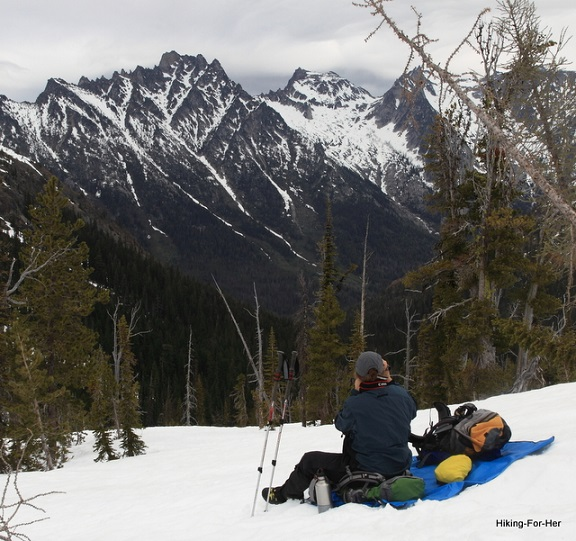 Female hiker sitting on a blue tarp in the snow with a big view of a snow covered mountain