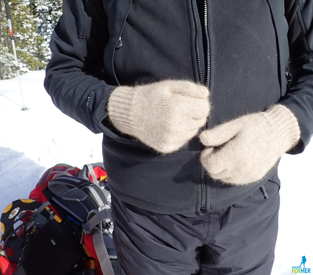 Possum down gloves on a hiker's hands with red backpack and yellow snowshoes on snowy ground