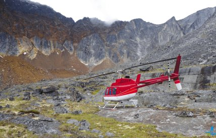 Red and white helicopter parked on rocks with rugged mountains all around