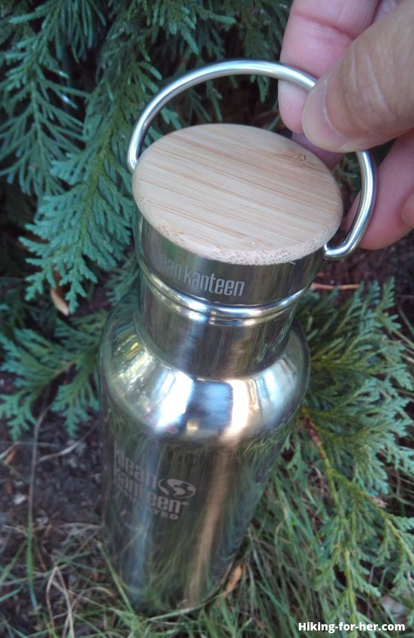 Klean Kanteen metal water bottle with bamboo cap and hiker's fingers grasping the cap's metal ring